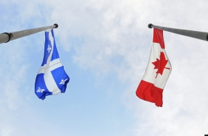 Quebec and Canada flying flags were photographed in Montreal on July 1, 2009. The Canadian Press Images/Denis Beaumont